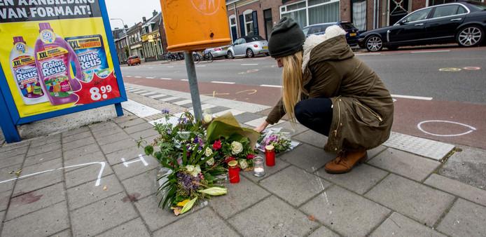 Een passant legt bloemen neer op de plek des onheils in Tilburg.