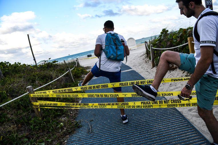 Mannen stappen over de politielinten die de toegang tot Miami Beach moeten verhinderen.