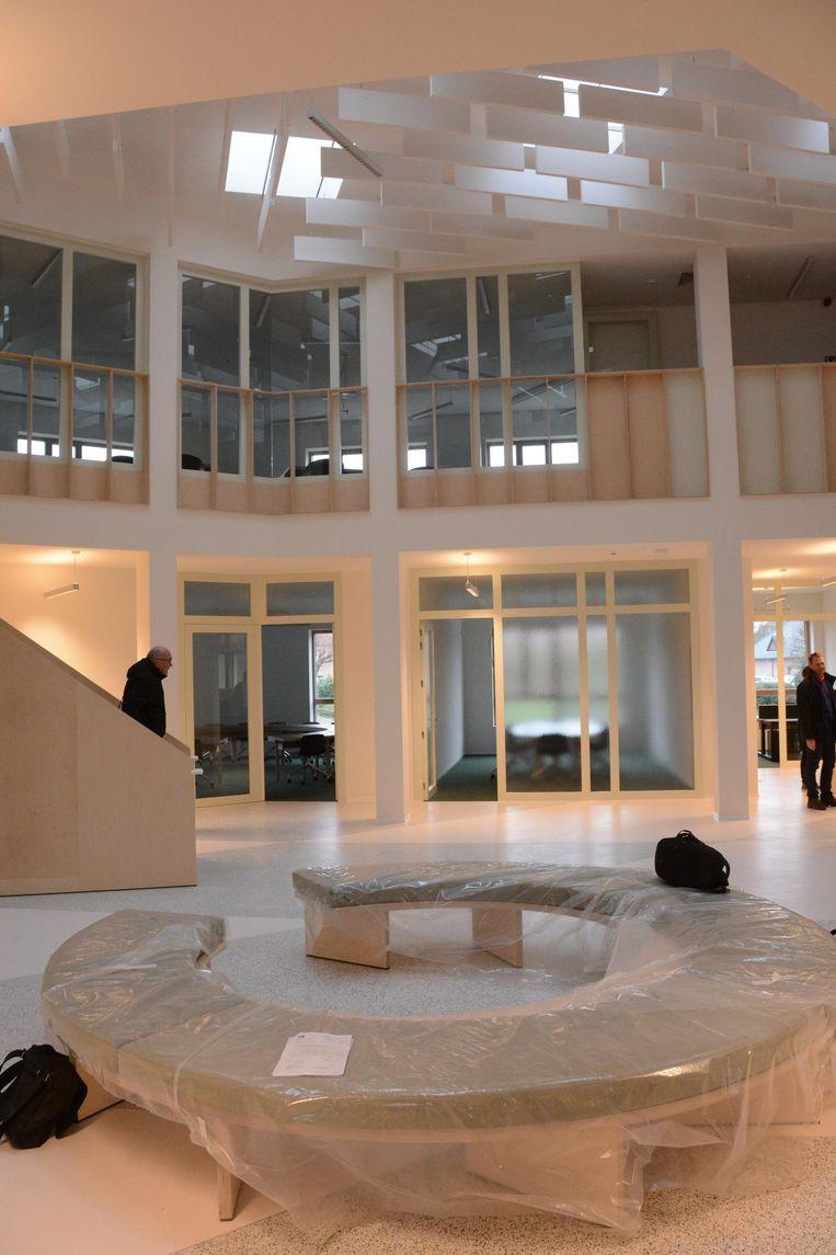 Centraal in de nieuwbouw is een grote open ruimte waar de bezoekers kunnen wachten en waarop alle kantoren uitkijken.