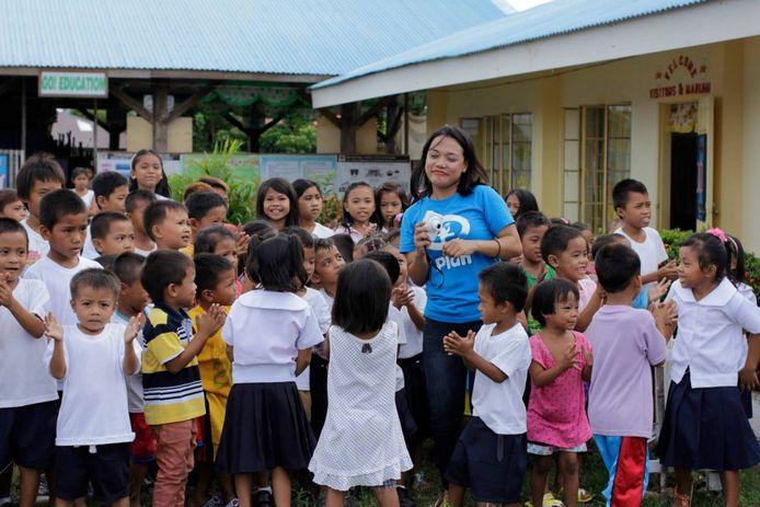 Een medewerker van Plan International bij een school op de Filipijnen.
