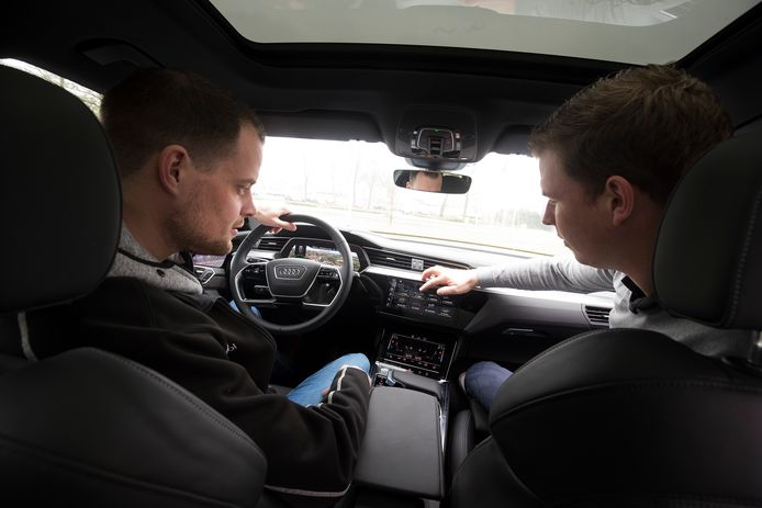 Testrijder Bart Mol (links) krijgt uitleg in de Audi E-tron.