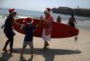 Ook in het Braziliaanse Rio de Janeiro is het zomer. De Kerstman, ofwel Papai Noel, heeft ondanks zijn drukke werkzaamheden toch even tijd gevonden om z'n surfplank te pakken.