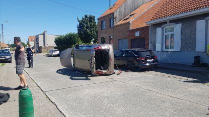 Auto belandt op zijkant na botsing met geparkeerde wagen, brandweer moet bestuurster bevrijden