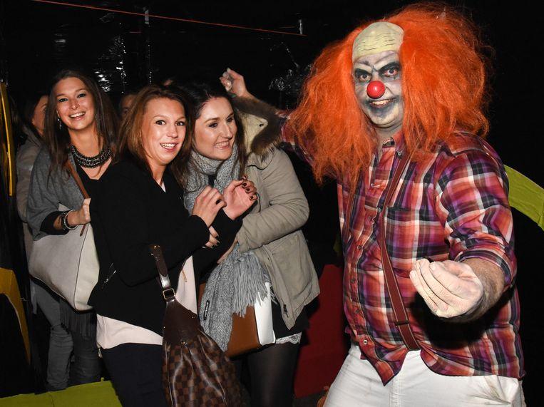 Deze Halloween-clown in gemeenschapscentrum Den Dries probeert enkele jongedames schrik aan te jagen.