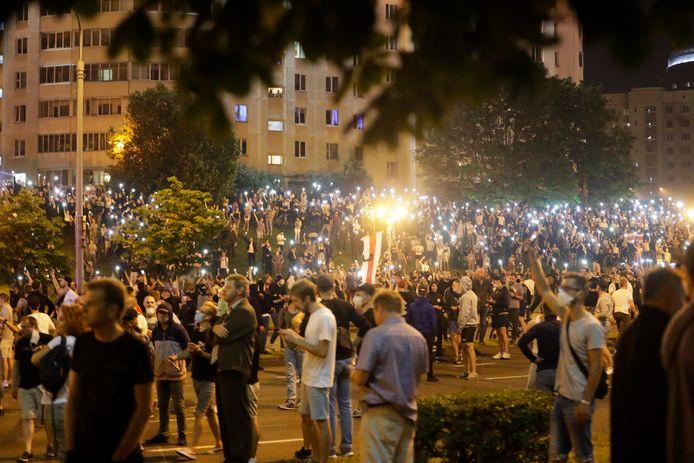 Mensen doen de lichtjes van hun telefoon aan tijdens het protest.