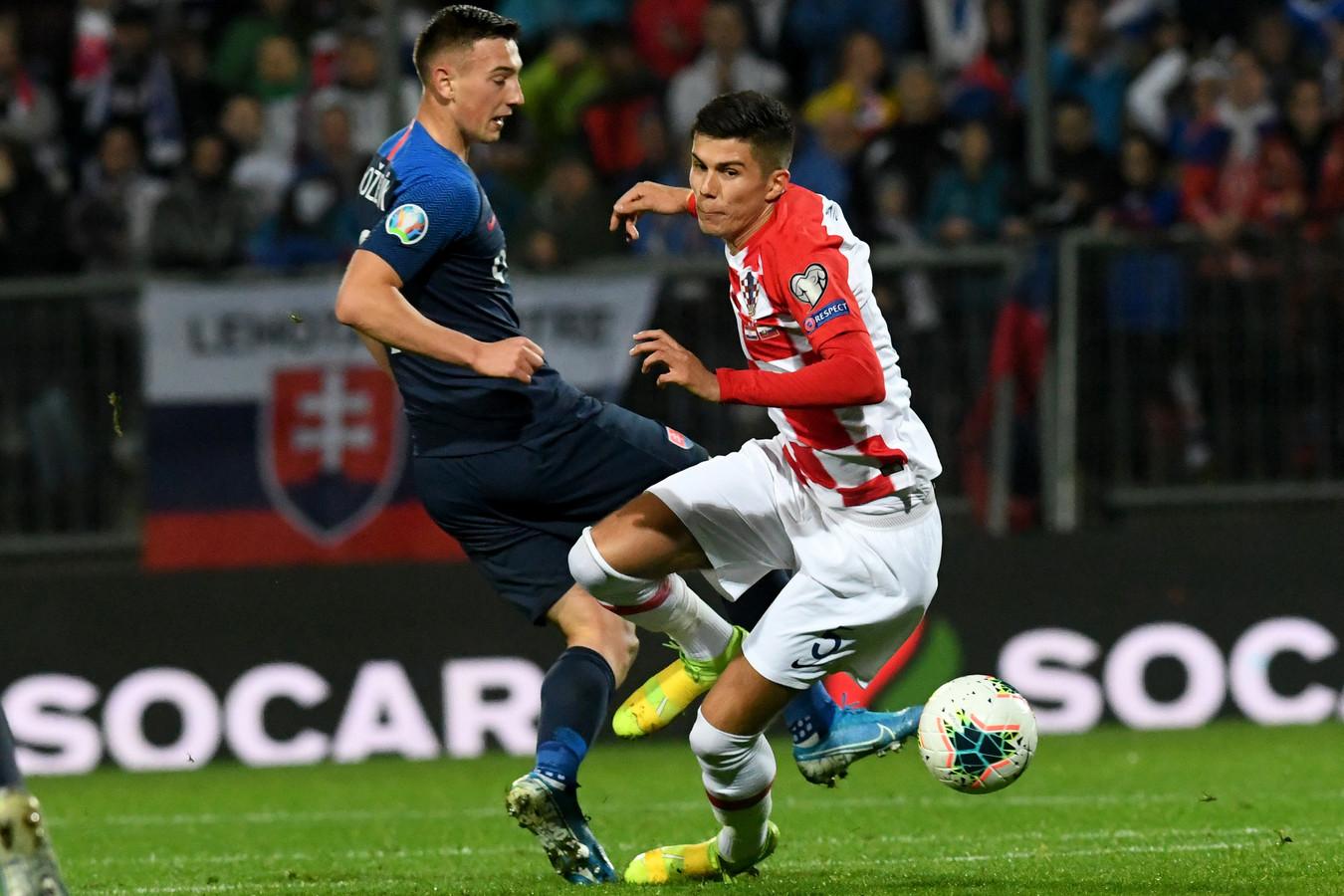 Robert Bozenik (l) namens Slowakije in duel met de Kroaat Dino Peric.