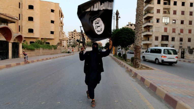Een Isis-strijder zwaait met de vlag van de terreurgroep in de Syrische stad Rakka. Beeld REUTERS