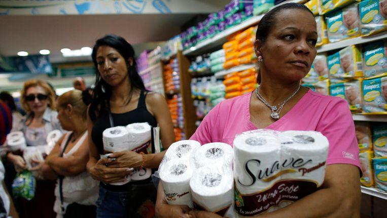 Klanten hamsteren wc-papier nadat een supermarkt in Caracas weer een lading heeft binnengekregen. Beeld REUTERS