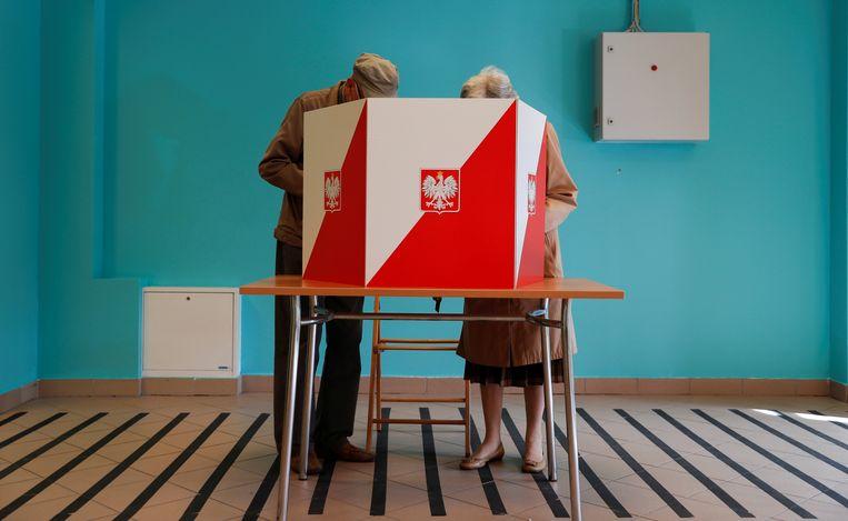 Kiezers brengen zondag hun stem uit in Warschau.  Beeld REUTERS