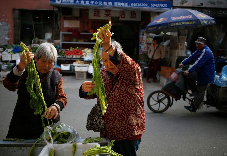 Markt in Peking. Door de vergrijzing en de eenkindpolitiek moeten veel gepensioneerde Chinezen voedsel uit hun moestuintje op de markt verkopen. Beeld EPA