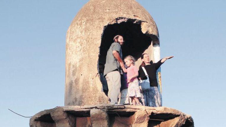 Joodse kolonisten zien uit over het land nabij Jenin, op de bezette Westelijke Jordaanoever, vanuit de vernielde minaret van een moskee. Beeld epa