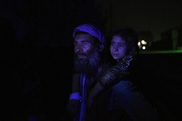 Een Afghaanse man draagt zijn gewonde dochter. Minstens vijftien mensen kwamen om bij een aanslag met een vrachtwagen vol explosieven Beeld afp
