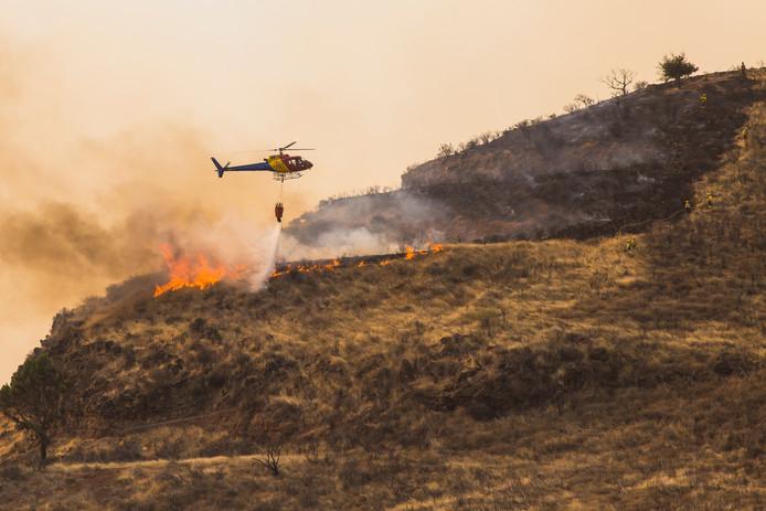 Met blusvliegtuigen en -helikopters wordt geprobeerd het vuur te doven