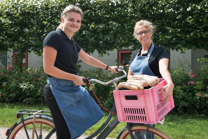 Britt van Gestel (l) op de speciale Bammetjesfiets, met begeleidster Shirley Wouters.