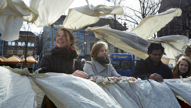Actievoerders hangen de vuile was buiten op het Plein voor de Tweede Kamer in maart 2013. De omwonenden van de stadssnelwegen hebben deze lakens weken van hun balkon laten hangen, om aan te tonen dat zij in vieze, ongezonde lucht moeten leven. Beeld ANP