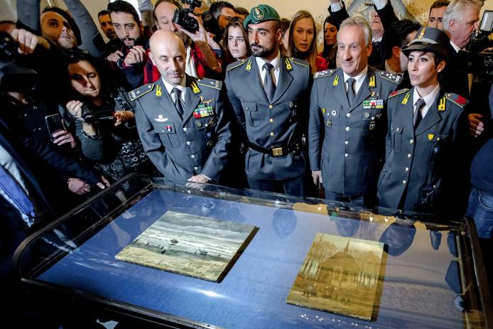 Italiaanse politiemensen poseren trots bij twee gestolen schilderijen van Vincent van Gogh die in 2016 werden teruggevonden bij een maffiaclan in Napels.