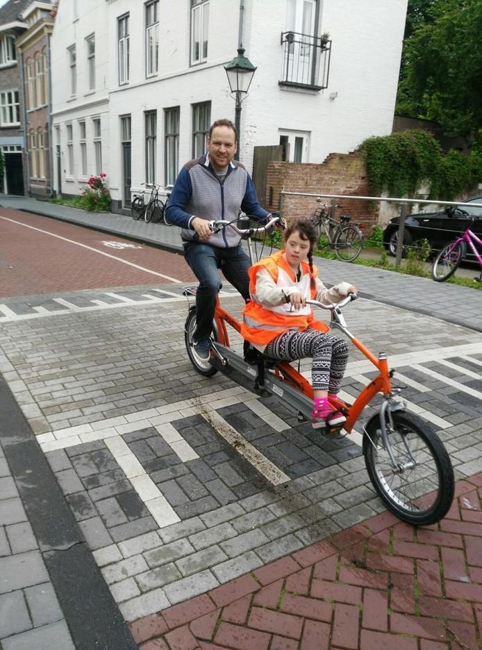 Benthe (11) met haar vader op de tandemfiets.