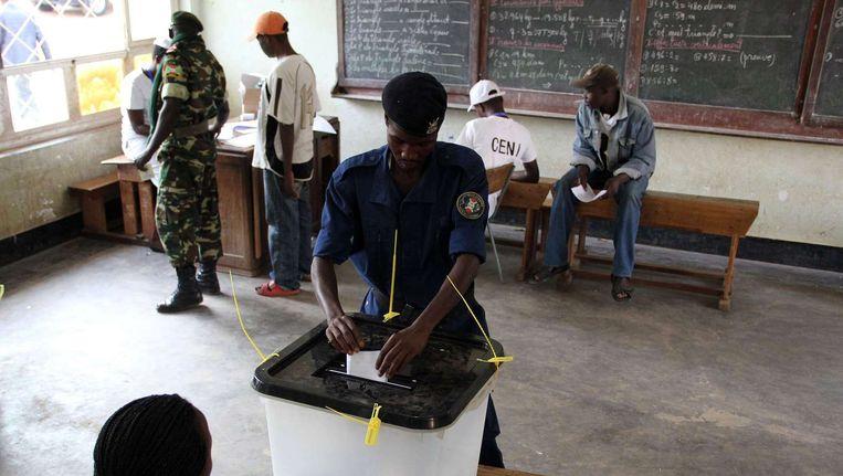 Een agent brengt zijn stem uit in een stembureau in Burundi. Beeld afp