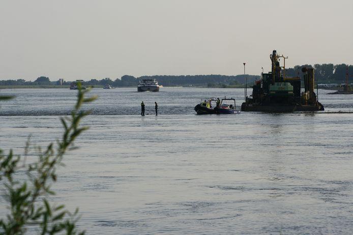 De politie is met boten aanwezig bij de Waal in Ophemert.