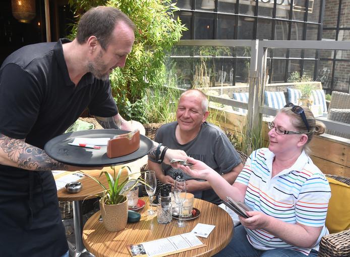 Koen Tesselaar van het Vlissingse Sint Jacobscafé rekent af met Alexandra Leiner en Ralf Keller uit Frankenthal. Duitsers zijn gul met fooien, zeggen horeca-ondernemers.