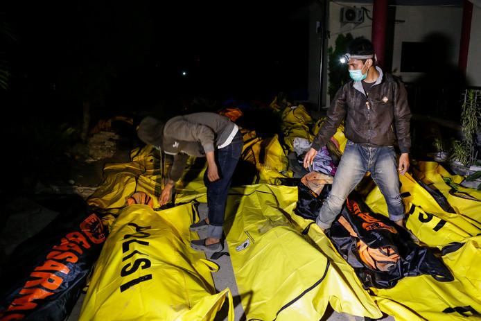 Dodelijke slachtoffers van de tsunami in bodybags op de grond.