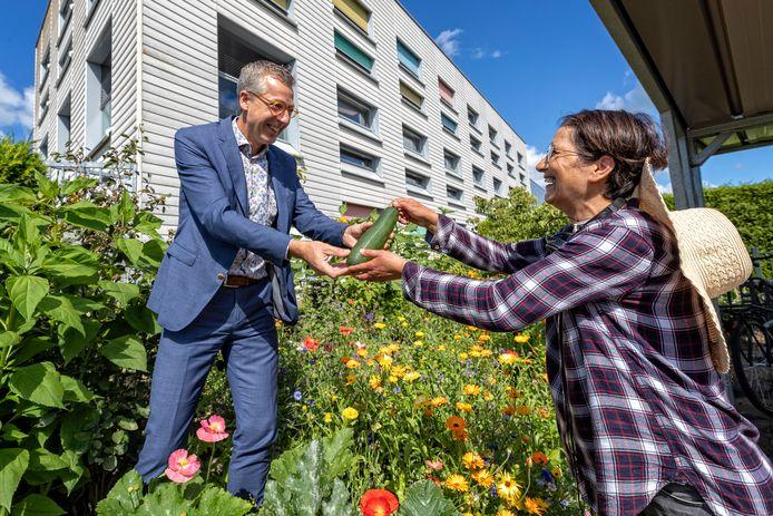 Scheidend directeur Jan de Vries van leerwerkbedrijf Rijnvicus krijgt van Sims Vasihzadeh als afscheidscadeau de eerste courgette uit de moestuin.