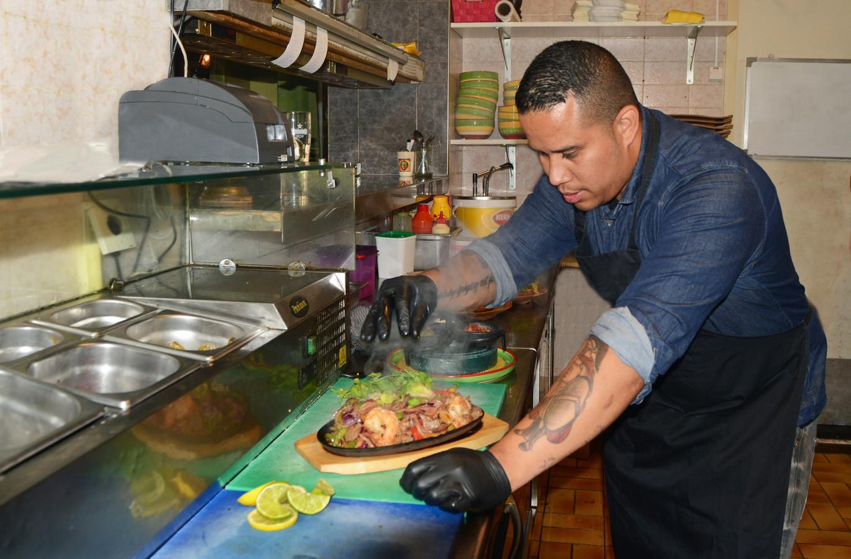 Ray Davila legt de laatste hand aan een gerecht in de keuken.