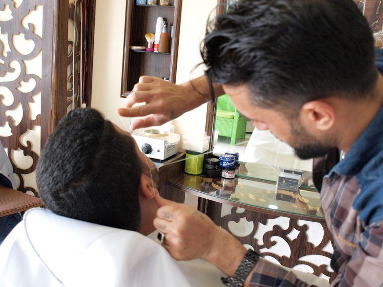 Kapper Serwan gebruikt een draadje om wat gezichtsharen weg te halen.  Beeld Judit Neurink