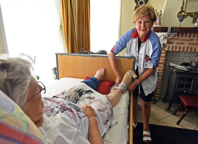 Verpleegkundige Winy Eijsackers trekt steunkousen aan bij Rita van Eetvelt.