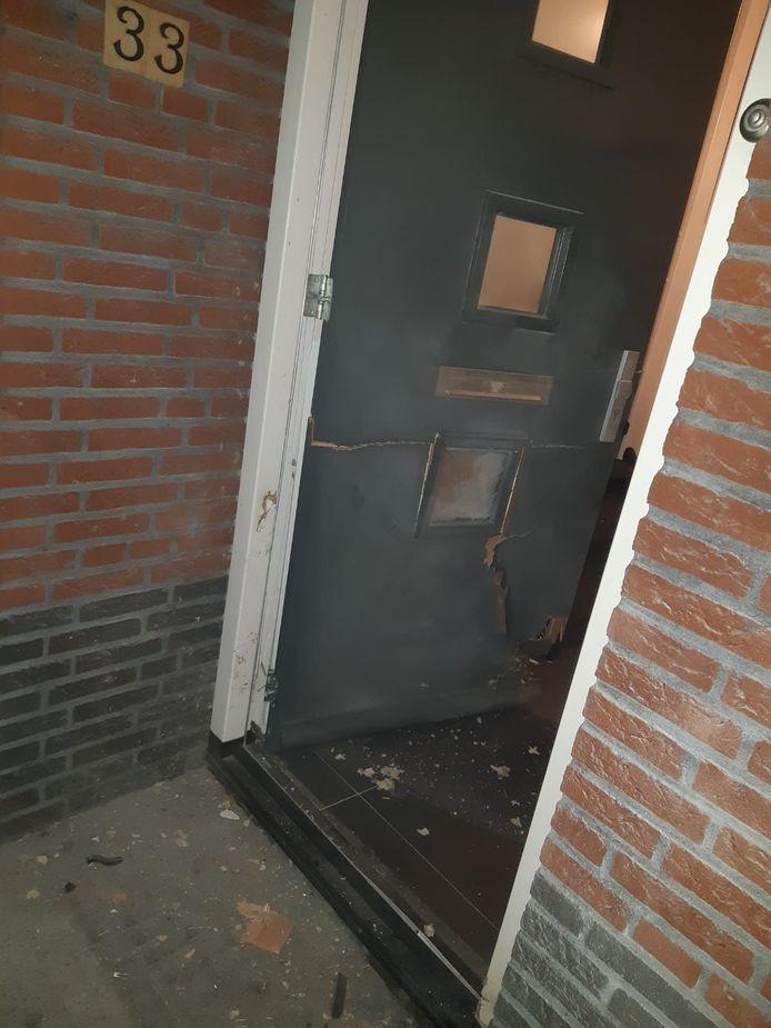 De beschadigde voordeur van de woning.