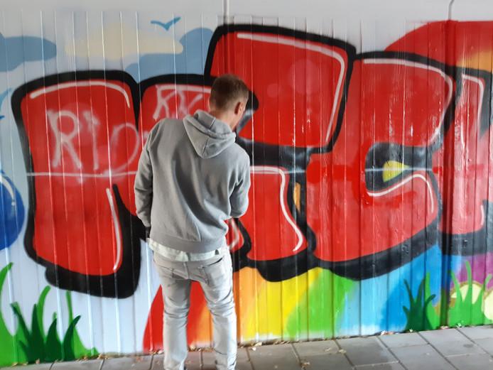 Graffiti-kunstenaar Sjaco Nagelkerke herstelt het kunstwerk dat jongeren in de fietstunnel in de Ganzeboomlaan aanbrachten.