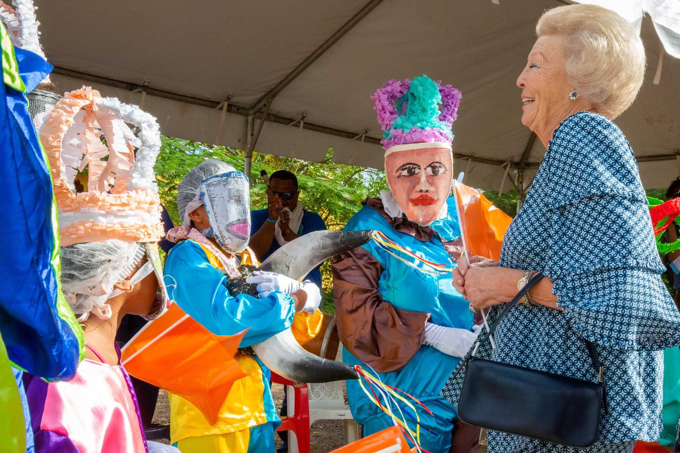 Prinses Beatrix vermaakt zich tijdens haar bezoek aan Bonaire met de maskers van de Maskerade van het bewonersinitiatief Hòfi Kultural.