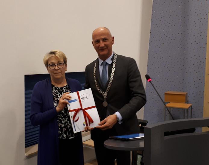 Dorpsraadvoorzitter Marion van Stiphout geeft de handtekeningen aan burgemeester Rob van der Zwaag