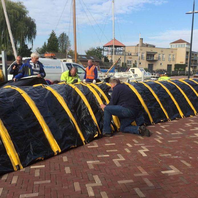 Medewerkers van Brabantse Delta zetten de dijk op bij de jachthaven van Steenbergen.