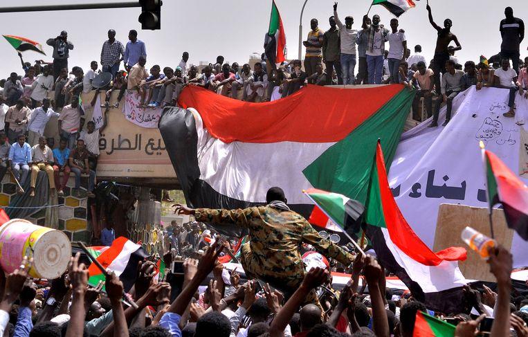 Een legerofficier wordt op handen gedragen door demonstranten die met nationale vlaggen zwaaien.