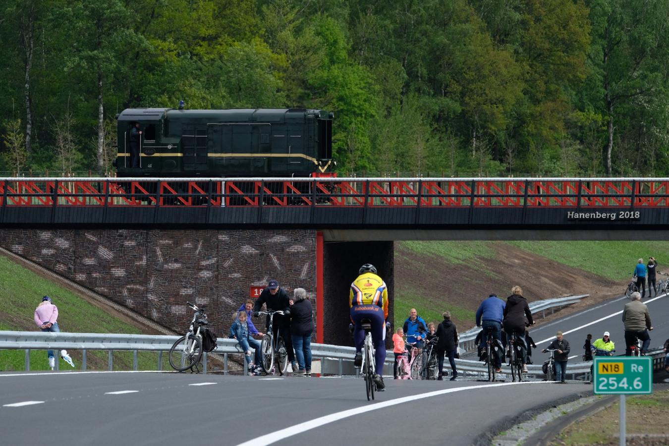 Fietsers, wandelaars en skaters maken gebruik van de N18. Op het viaduct een trein van de MBS.
