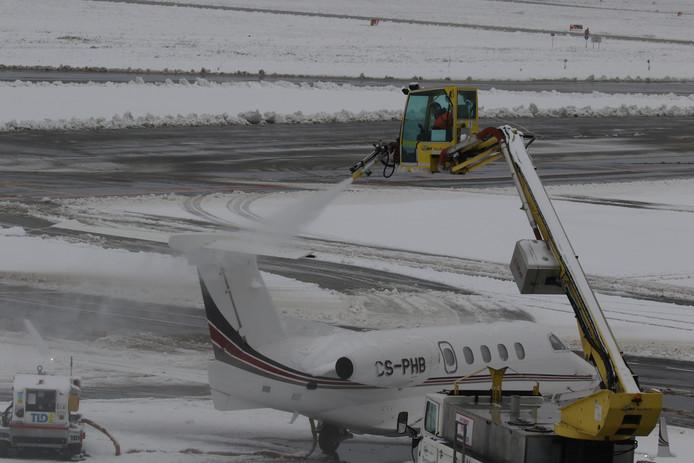 Een vliegtuig op Eindhoven Airport wordt ijs- en sneeuwvrij gemaakt.