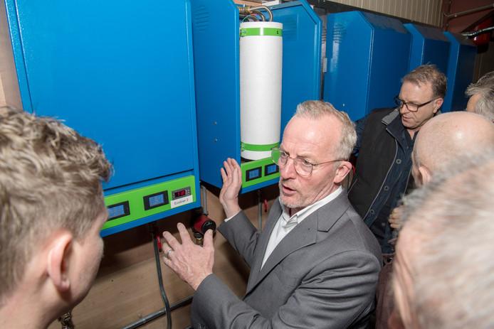 Wil Schottman poseert bij de nieuwe duurzame ketels die hij uitvond.