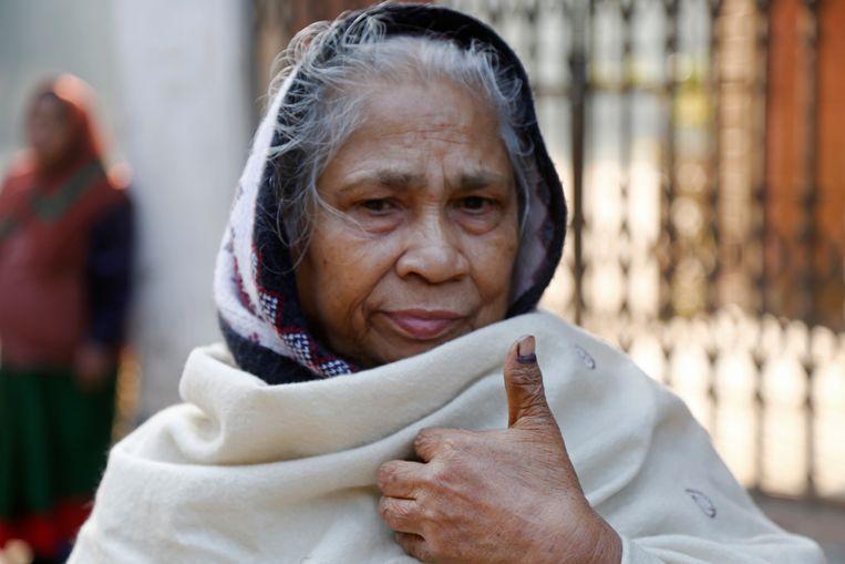 Een vrouw laat zien dat ze gestemd heeft door de inkt op haar vinger te tonen.