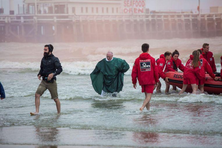 De zegening is voorbij, ook de deken waadt naar het strand. Redders trekken de boot op het droge.