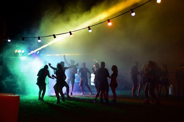 Jongeren bouwen een eigen festival in een weiland. Als iemand bij meerdere gelegenheden geen afstand hield, zie dan de bron nog maar te achterhalen. Beeld Marcel van den Bergh / de Volkskrant