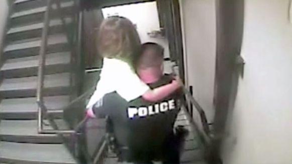 Een agent brengt het ontvoerde meisje in veiligheid.