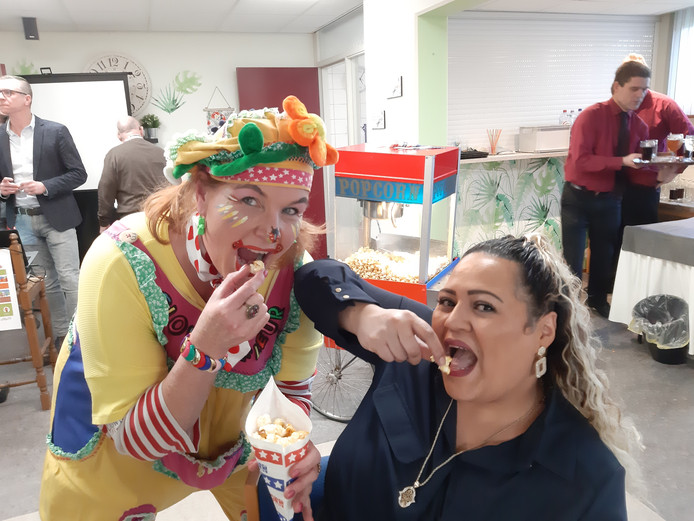 Clown Fleur en wijkbewoonster Soufia Che delen een zakje popcorn met elkaar in het nieuwe kantoor van Talis in Wijchen-Zuid.
