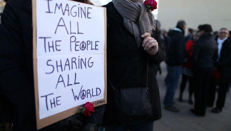 Een vrouw houdt een bord vast met daarop tekst uit het lied