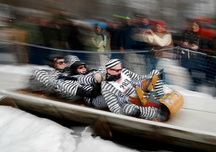 Tijdens de Amerikaanse 'Tobboggan Championships' in Maine knallen vierpersoons sledes de besneeuwde heuvel af onder het motto: als je maar beneden komt. Op de rodelbaan in Camden is het gebruikelijk dit in carnavalskostuum te doen. Foto Robert F. Bukaty
