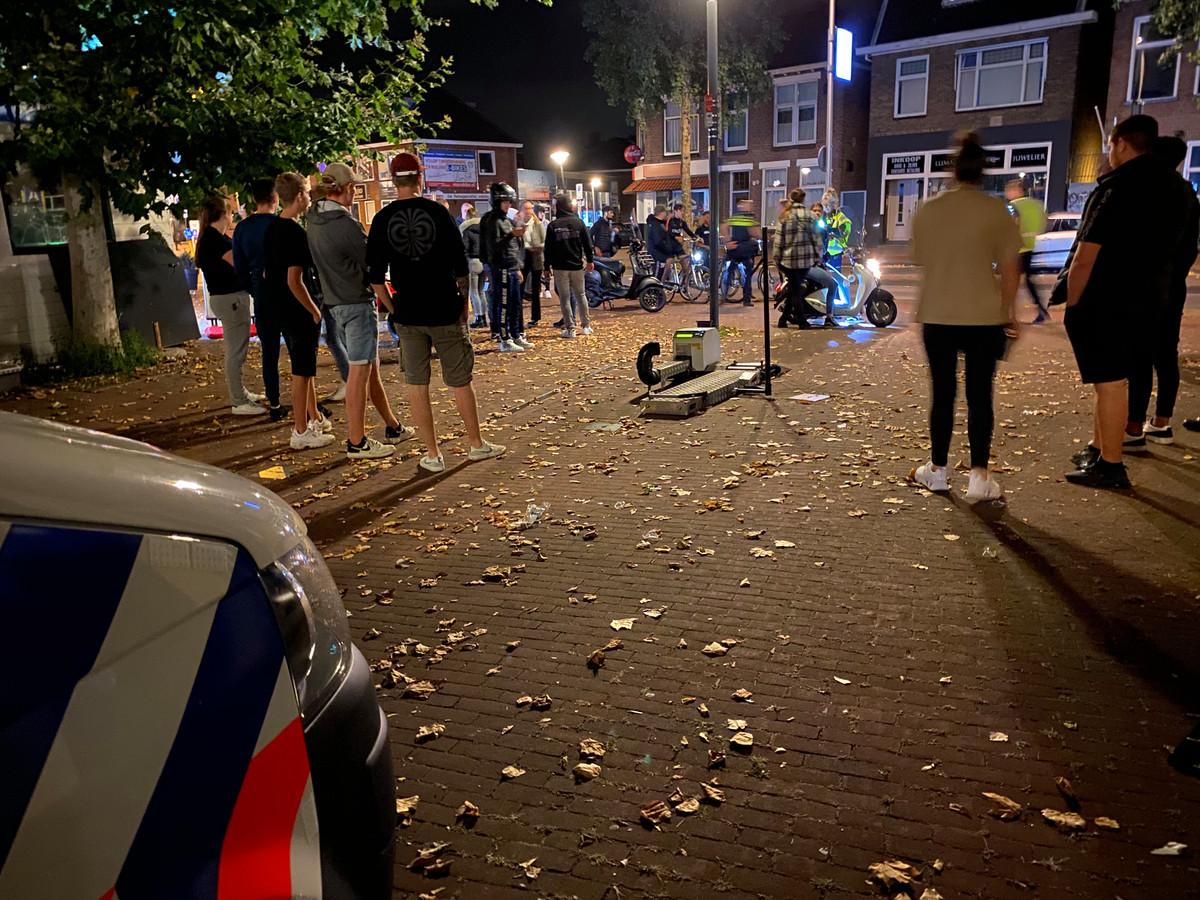 Jongeren kijken toe hoe de politie scooters onderwerpt aan een inspectie.
