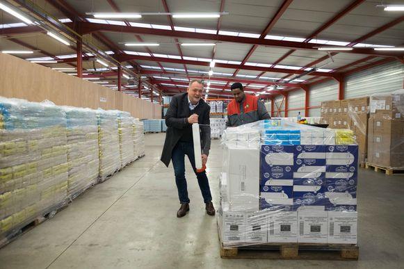 Schepen Fons Duchateau helpt even bij het inwikkelen van een pallet in het opslagcentrum.
