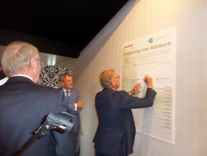 Burgemeester Yves de Boer van Werkendam tekent de verklaring van Almkerk. Zijn collega's van Aalburg en Woudrichem kijken toe.