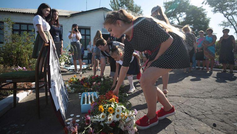 Dorpelingen uit Petropavlivka in separatistisch gebied in Oekraïne leggen twee jaar na de MH17-ramp bloemen tijdens een herdenking van de slachtoffers. Beeld afp