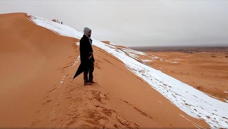 Een man kijkt naar beneden vanaf de besneeuwde toppen van een zandduin. Beeld Reuters